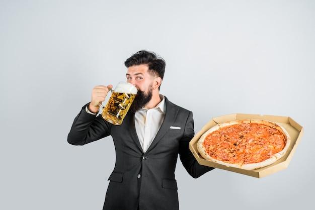 Restauracja lub pizzeria. czas pizzy. zaskoczony mężczyzna z brodą trzyma pyszną pizzę w pudełku i zimne piwo. koncepcja dostawy pizzy. fast food. włoskie jedzenie. brodaty mężczyzna z pyszną pizzą i piwem w rękach.
