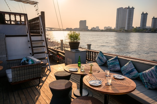 Restauracja na pokładzie ze stołem jadalnym, sofą, naczyniami, sztućcami na tarasie statku nad rzeką wieczorem