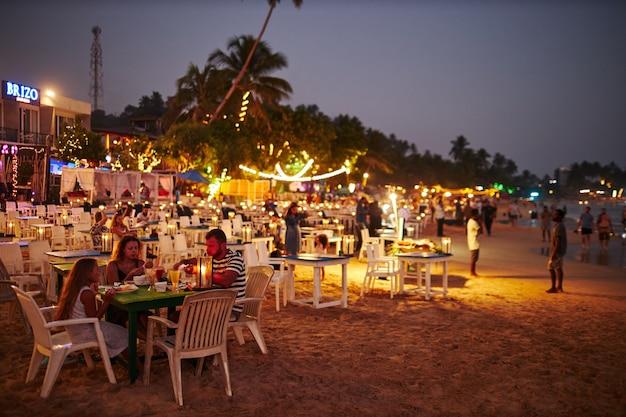 Restauracja na świeżym powietrzu na plaży podczas zachodu słońca.