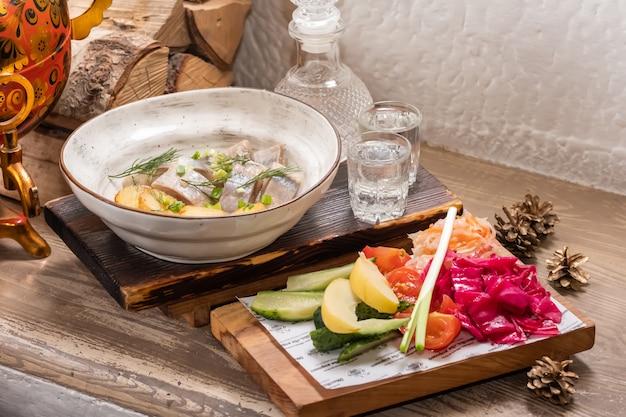 Restauracja seafood menu z solonym śledziem z krążkami cebuli i gotowanym pokrojonym w kostkę ziemniakiem na eleganckim talerzu restauracyjnym z zestawem zimnej wódki alkoholowej i różnorodnych marynowanych.