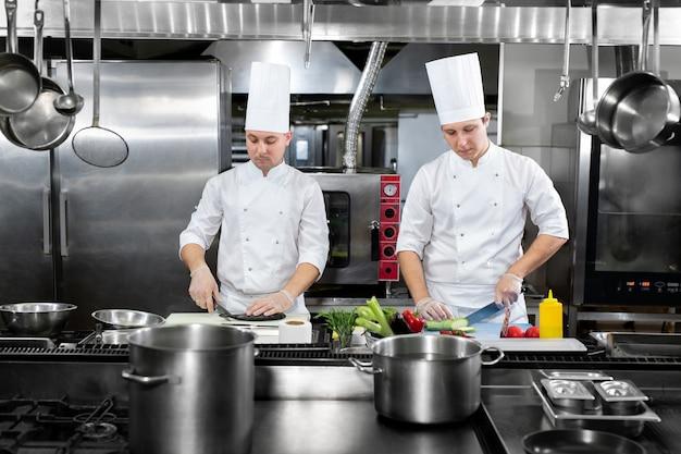 Restauracja zajęta kuchnia, szefowie kuchni i kucharze pracujący nad swoimi potrawami