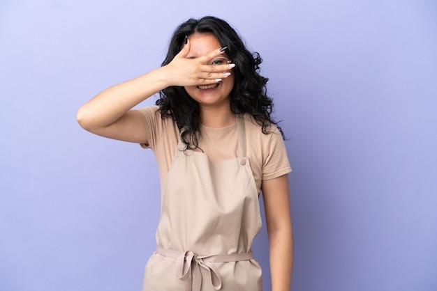 Restauracyjny azjatycki kelner na fioletowym tle zakrywający oczy rękami i uśmiechnięty