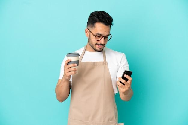 Restauracyjny kelner kaukaski mężczyzna na białym tle na niebieskim tle trzymający kawę na wynos i telefon komórkowy