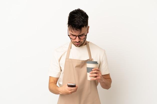 Restauracyjny kelner kaukaski mężczyzna na białym tle trzymający kawę na wynos i telefon komórkowy