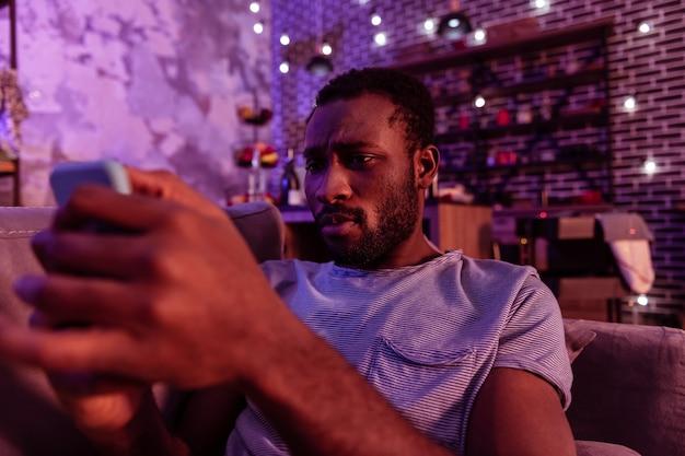 Resztki i porcje. ciekawy brodaty mężczyzna o czarnych włosach trzymający telefon komórkowy i obserwujący zdjęcia z ostatniej nocy