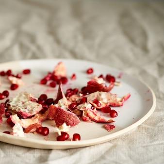 Resztki jedzenia z czyszczenia granatu i nasion na talerzu na stole pokrytym pomarszczonym beżem