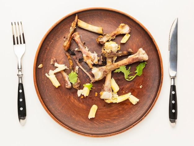 Resztki kości podudzia z kurczaka na talerzu