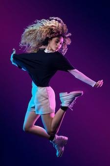 Retrato a bailarina latina en estudio con luces de colores