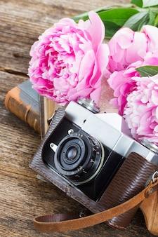 Retro aparat fotograficzny z książkami i świeżymi kwiatami piwonii