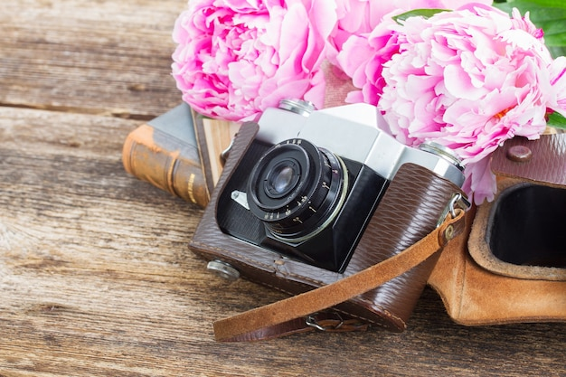 Retro aparat fotograficzny z książkami i świeżymi różowymi kwiatami piwonii