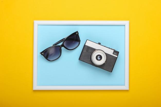Retro aparat i okulary przeciwsłoneczne na żółtej powierzchni z ramką