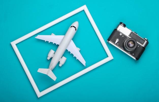 Retro aparat i samolot w białej ramce na niebieskiej powierzchni