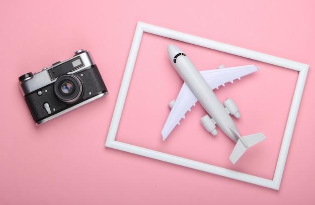 Retro aparat i samolot w białej ramce na różowej powierzchni