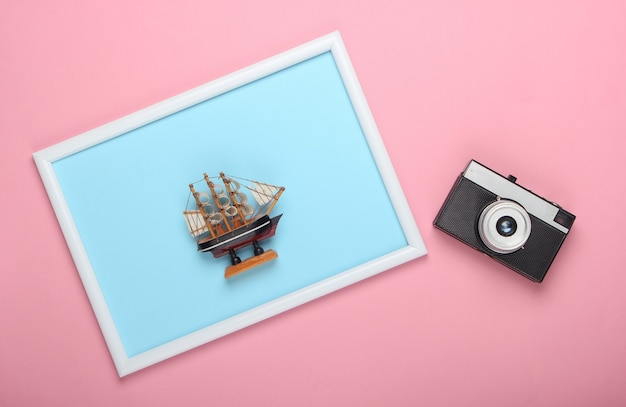 Retro aparat i statek zabawki na różowej powierzchni z ramką