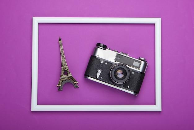 Retro aparat i statuetka wieży eiffla w białej ramce na fioletowej powierzchni