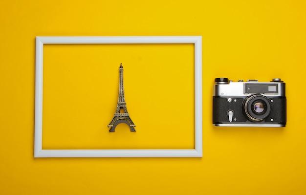 Retro aparat i statuetka wieży eiffla w białej ramce na żółtej powierzchni