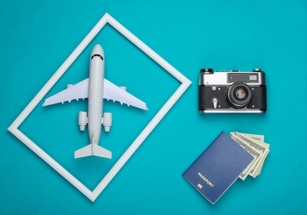 Retro aparat, paszport i samolot w białej ramce na niebieskiej powierzchni