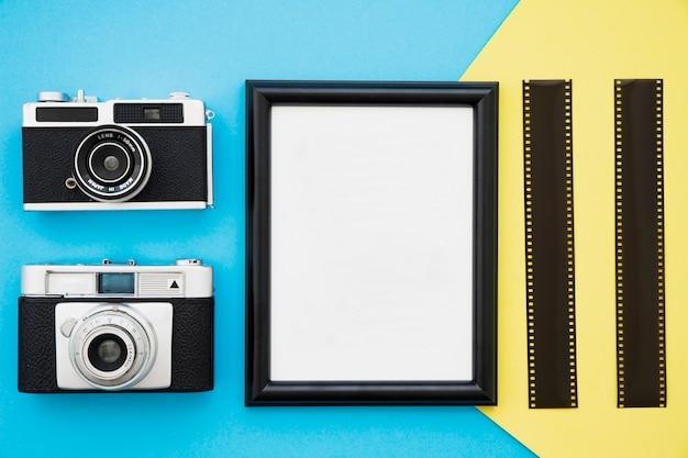 Retro aparaty fotograficzne i film w pobliżu ramki