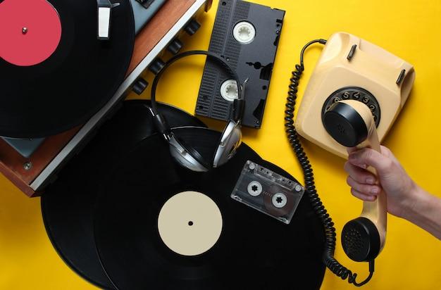 Retro atrybuty z lat 80. na żółtym tle. ręka trzyma słuchawkę rocznika telefonu obrotowego na tle odtwarzacza winylu, wideo, kasety audio, słuchawki. widok z góry