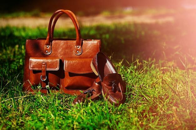 Retro brązowe buty i skórzana torba mężczyzny w jasnej kolorowej letniej trawie w parku