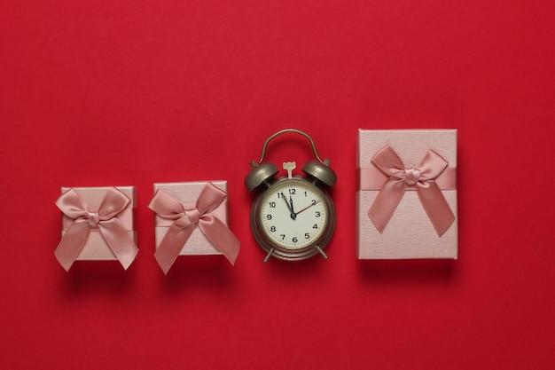 Retro budzik i pudełka z kokardą na czerwonym tle. 11:55. nowy rok, koncepcja bożego narodzenia. widok z góry