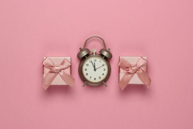 Retro budzik i pudełka z kokardą na różowym pastelowym tle. 11:55. nowy rok, koncepcja bożego narodzenia. widok z góry
