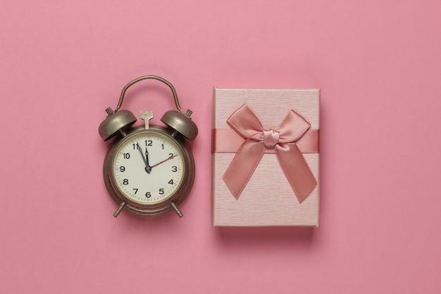 Retro budzik i pudełko z kokardą na różowym pastelowym tle. 11:55. nowy rok, koncepcja bożego narodzenia. widok z góry