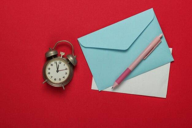 Retro budzik, koperta list mikołaja na czerwonym tle. 11:55. nowy rok, koncepcja bożego narodzenia. widok z góry