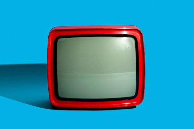 Retro czerwona telewizja na niebieskim tle