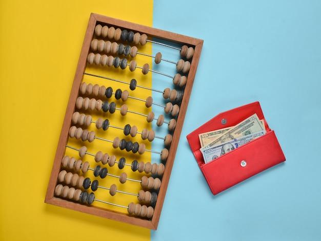 Retro drewniane liczydło, czerwona skórzana torebka z banknotów dolarowych na niebieskim papierze