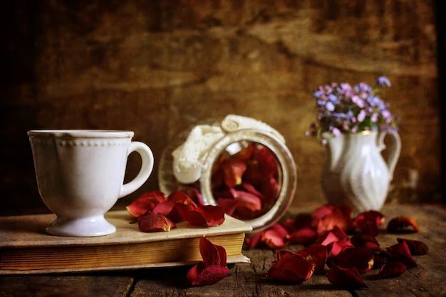 Retro efekt na zdjęciu vintage herbaty z suchym płatkiem róży