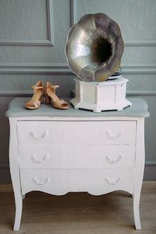 Retro foto-gramofon na białej drewnianej komodzie.
