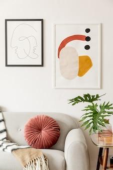 Retro i vintage wnętrze salonu z designerską szarą sofą, stołem, lampą, kocem i galerią ramek plakatów na białych ścianach
