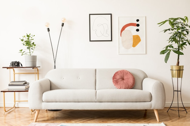 Retro i vintage wnętrze salonu z designerską szarą sofą, stołem, lampą, regałem, kocem i galerią ramek plakatów na białych ścianach