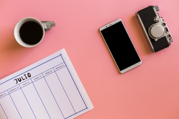Retro kamera blisko smartphone, filiżanka napój i kalendarz