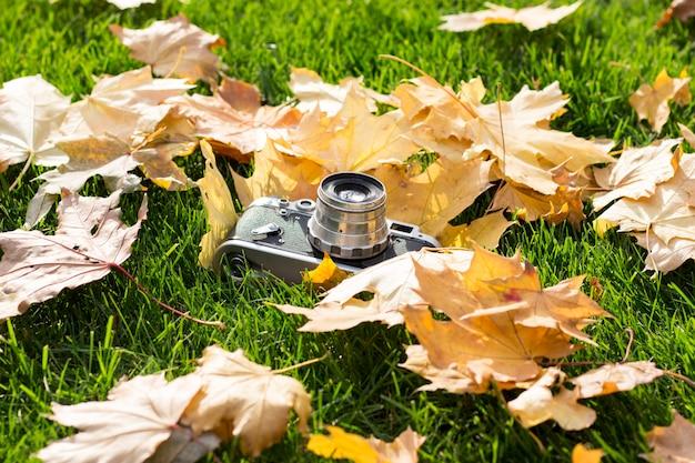 Retro kamera na trawniku z żółtymi jesień liśćmi. pojęcie początku jesieni i początku jesieni liści