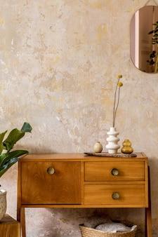 Retro kompozycja wnętrza salonu z drewnianą komodą vintage, lustrem w kolorze złotym, rośliną, rattanowym koszem, kratą, dekoracją i eleganckimi dodatkami osobistymi w wystroju domu wabi sabi.