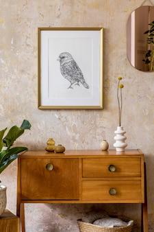 Retro kompozycja wnętrza salonu z drewnianą komodą vintage, złotym różowym lustrem, makietą ramy plakatu, rośliną, dekoracją i eleganckimi akcesoriami osobistymi w wystroju domu wabi sabi.