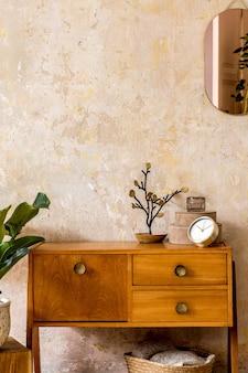 Retro kompozycja wnętrza salonu z drewnianą komodą vintage, złotym różowym lustrem, rośliną, rattanowym koszem, kratą, dekoracją i eleganckimi dodatkami osobistymi w wystroju domu wabi sabi.