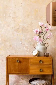 Retro kompozycja wnętrza salonu z drewnianą komodą w stylu vintage, złotym różowym lustrem, dekoracją kosza z rattanu i eleganckimi dodatkami osobistymi w wystroju domu wabi sabi