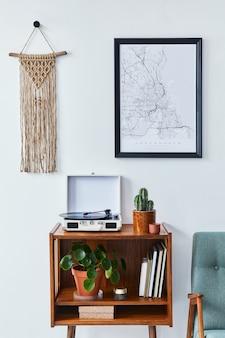Retro kompozycja wnętrza salonu z mapą plakatową, drewnianą półką, książką, makramą, fotelem, rośliną, kaktusami, magnetofonem i akcesoriami osobistymi w stylowym wystroju domu.