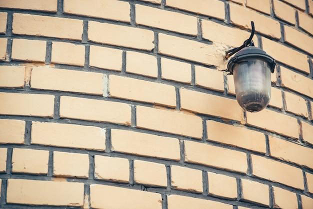Retro latarnia uliczna na beżowym ściana z cegieł budynku zakończenie up z kopii przestrzenią. niedoskonałe zaokrąglone cegły z klasycznym oświetleniem ulicznym.