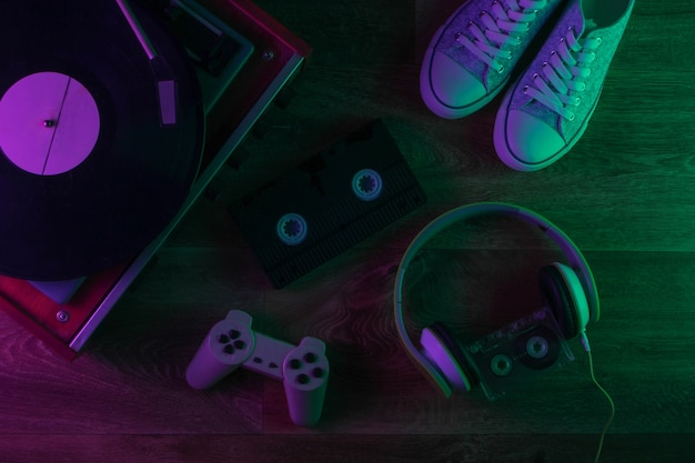 Retro media i staromodne rzeczy na drewnianej podłodze z zielono-fioletowym światłem neonowym