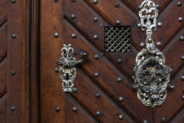 Retro metalowa klamka z brązowymi drewnianymi drzwiami. miejsce na tekst