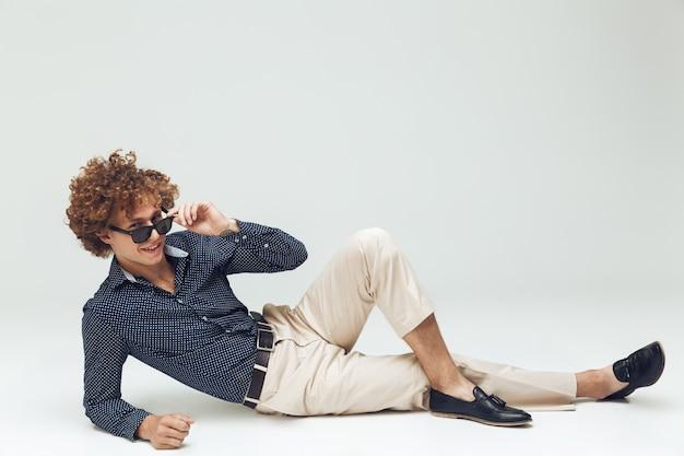 Retro mężczyzna ubrany w koszulę leży na podłodze i pozowanie
