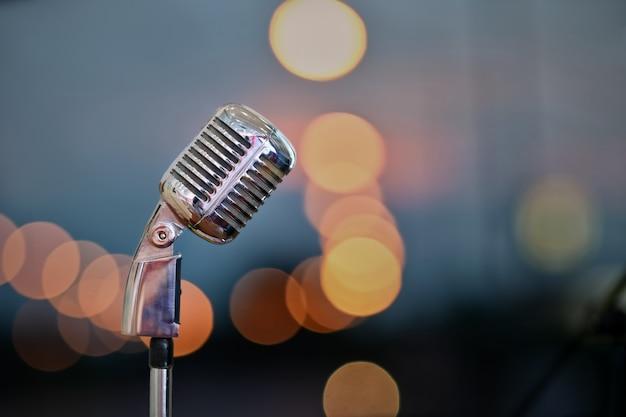 Retro mikrofon na scenie nad zamazanym bokeh tłem.