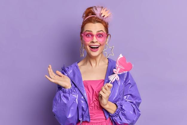 Retro modelka ubrana w stylu lat dziewięćdziesiątych ma szczęśliwy wyraz nostalgii, trzyma pyszne cukierki na żywym fioletowym tle. trendy w modzie. ruda dziewczyna w modnej fioletowej kurtce okulary przeciwsłoneczne