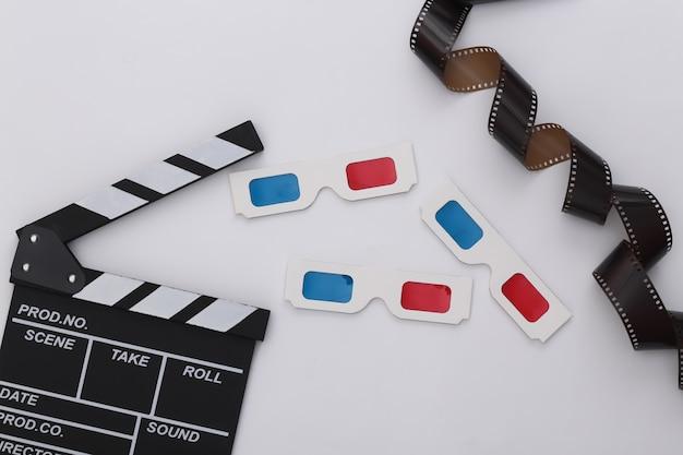 Retro movie clapper board, okulary 3d i taśma filmowa na białym tle. produkcja filmowa, produkcja filmowa. lata 80. widok z góry