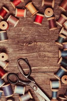 Retro nożyczki, nici tekstylne i do szycia na drewnianym stole z miejscem na kopię