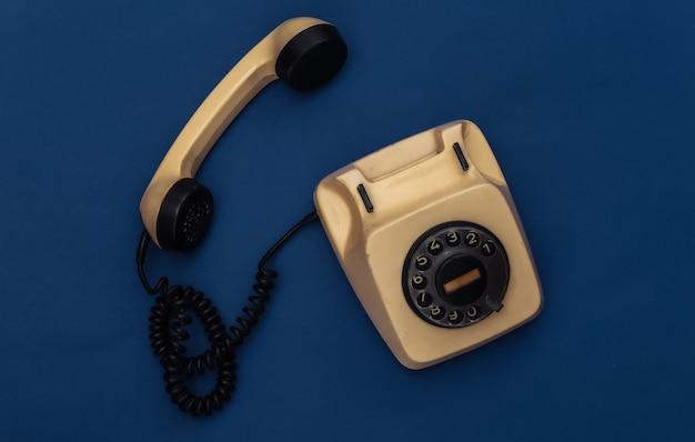 Retro obrotowy telefon na klasycznym niebieskim tle. kolor 2020.